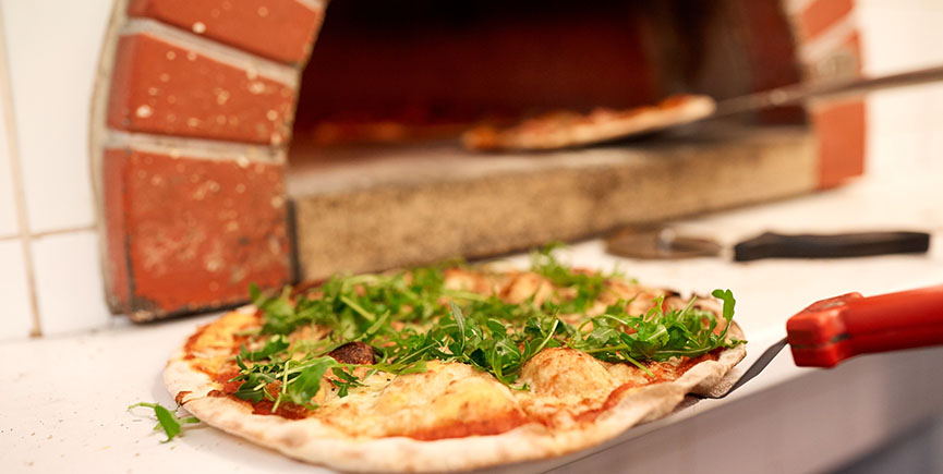 baked pizza on peel at pizzeria oven