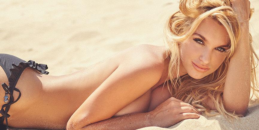 Beautiful girl lying on sandy beach in panties