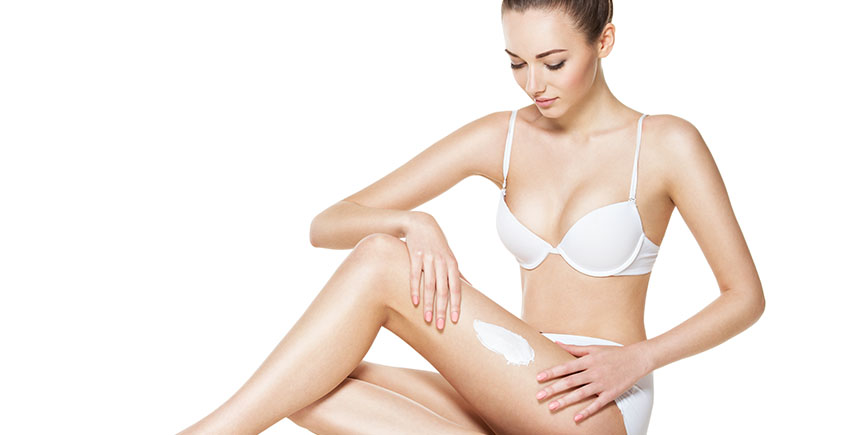 beautiful young woman depilating legs by waxing