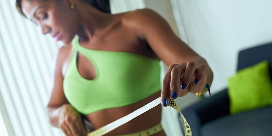 Black Woman Measuring Waist With Yellow Tape