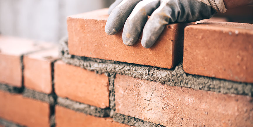 Close up of industrial bricklayer installing bricks on construct