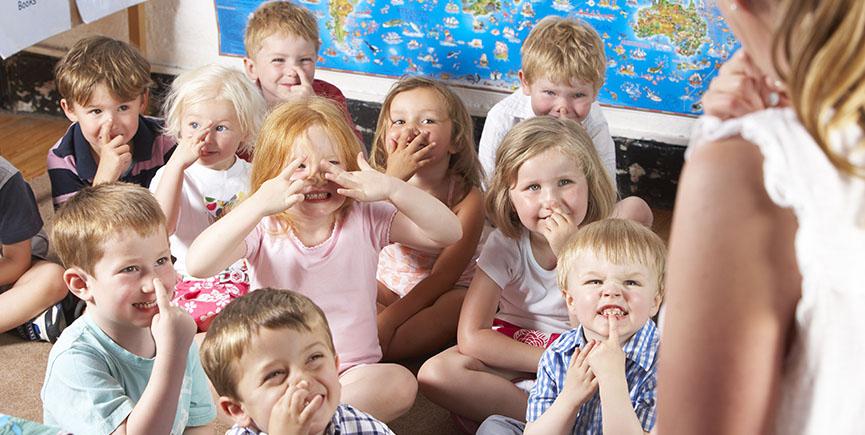 Montessori/Pre-School Class Listening to Teacher on Carpet