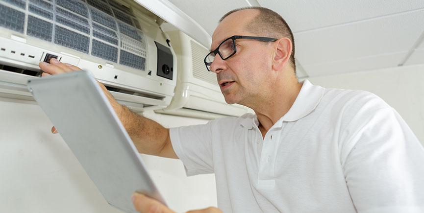 man checking airconditioning manual while using it