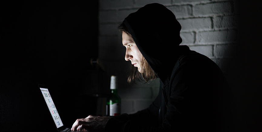 Man using laptop computer at home indoors at night