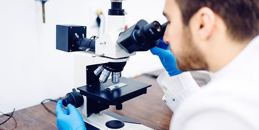 Scientist looking through a microscope in a laboratory, testing