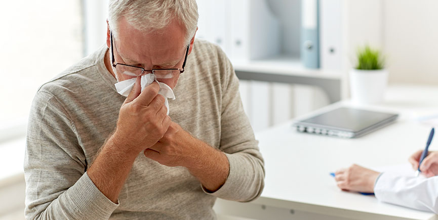 senior man blowing nose with napkin at hospital