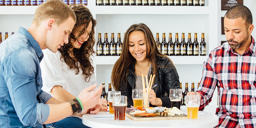 Smiling company at table with beer