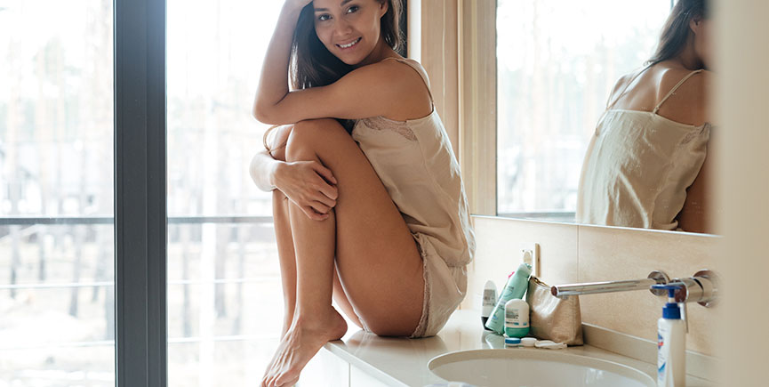 Smiling gorgeous young woman sitting in bathroom