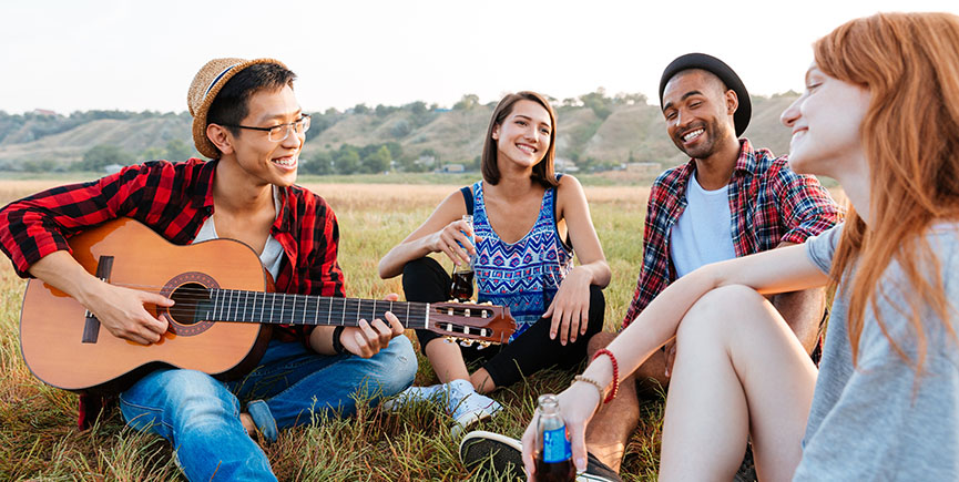 Smiling young friends playing guitar and singing outdoors