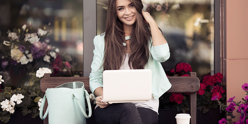 Portrait Of A Smiling Young Woman Sitting On The Bench And Using