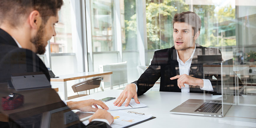 Two happy businessmen discussing business plan on meeting in office