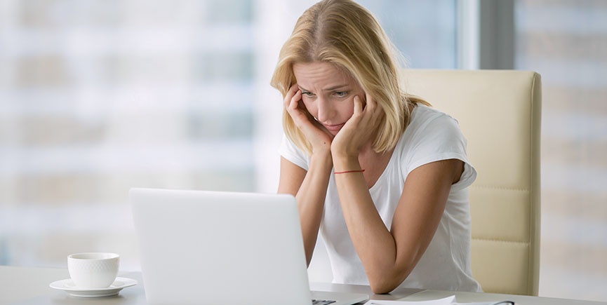 Young hopeless woman at laptop